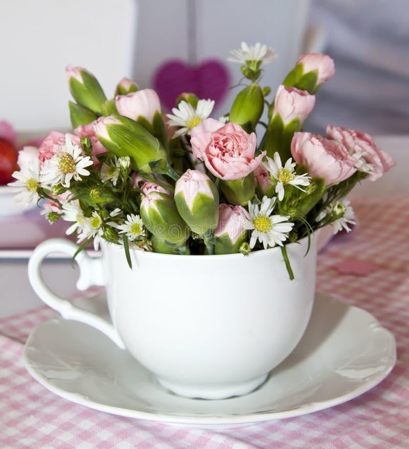 Fleurs dans une cuvette sur un rose images libres de droits