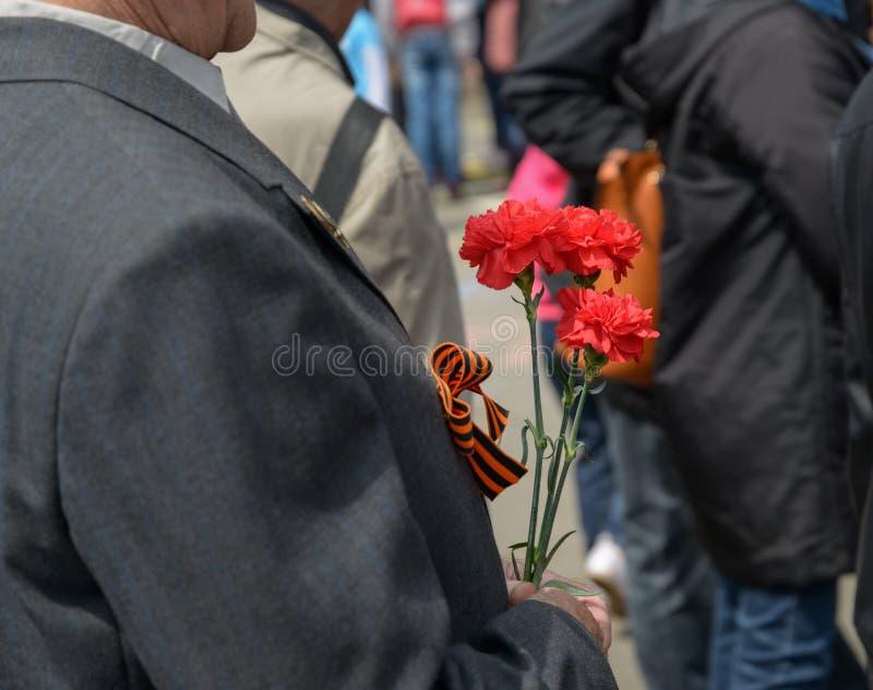 Fleurs dans une main de vétéran non identifié photo libre de droits