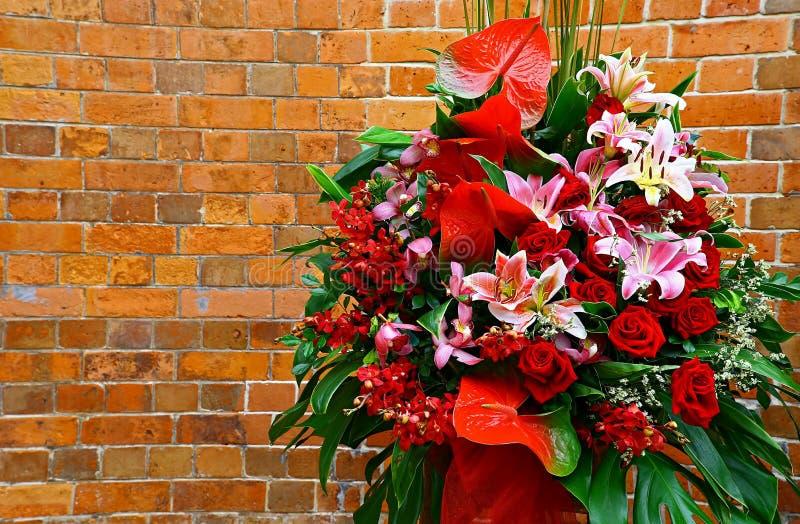 Fleurs de bouquet contre le mur de briques sinueux photo stock