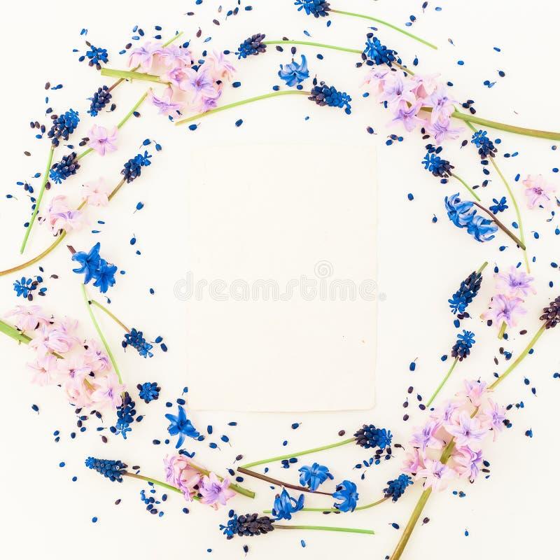 Fleurs de cadre floral rond et carte bleues et roses sur le fond blanc Configuration plate, vue supérieure Blog, media social ou  photo libre de droits