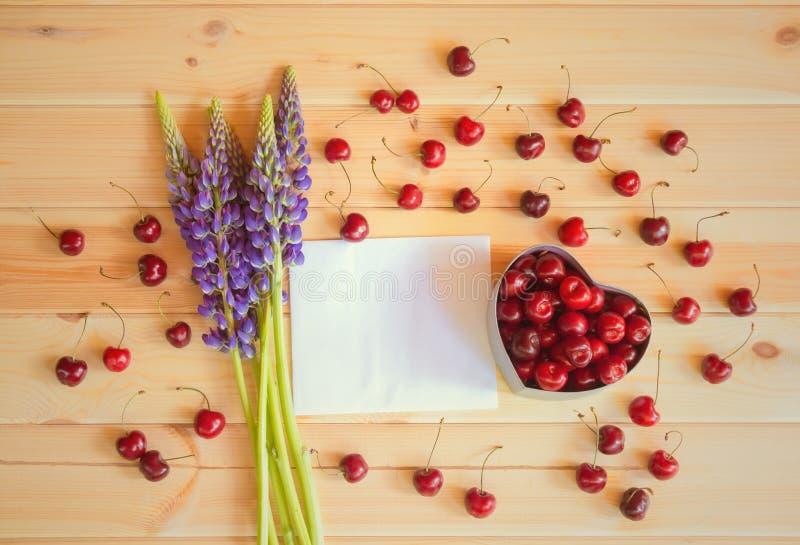 Fleurs de carte de loup et vide pour votre texte et de boîte-cadeau de forme de coeur avec la cerise fraîche sur le fond en bois images stock