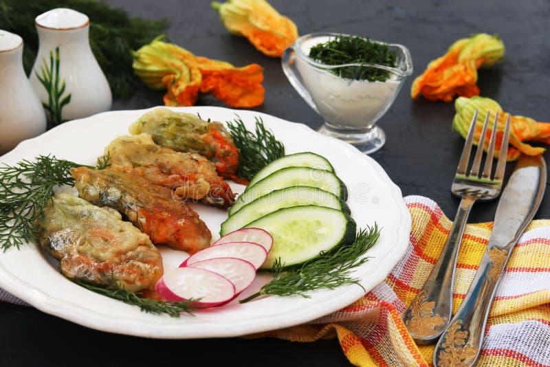 Fleurs de courgette, cuites en p?te lisse, tranches de concombres et radis d'un plat photo libre de droits