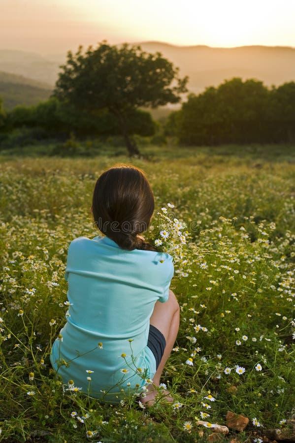 Fleurs de fixation de fille dans le domaine au coucher du soleil photographie stock libre de droits