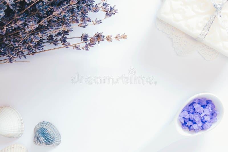 Fleurs de lavande, de savon blanc, de sel de mer dans une cuillère et de coquillages sur le fond blanc de tha photos libres de droits