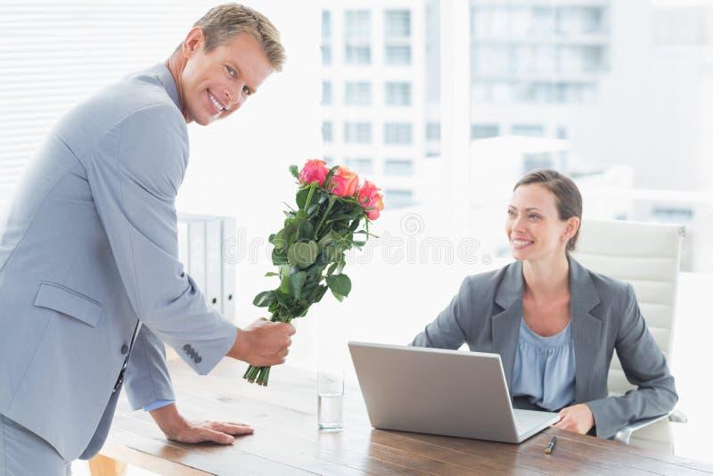 Fleurs de offre d'homme d'affaires à son collègue images libres de droits