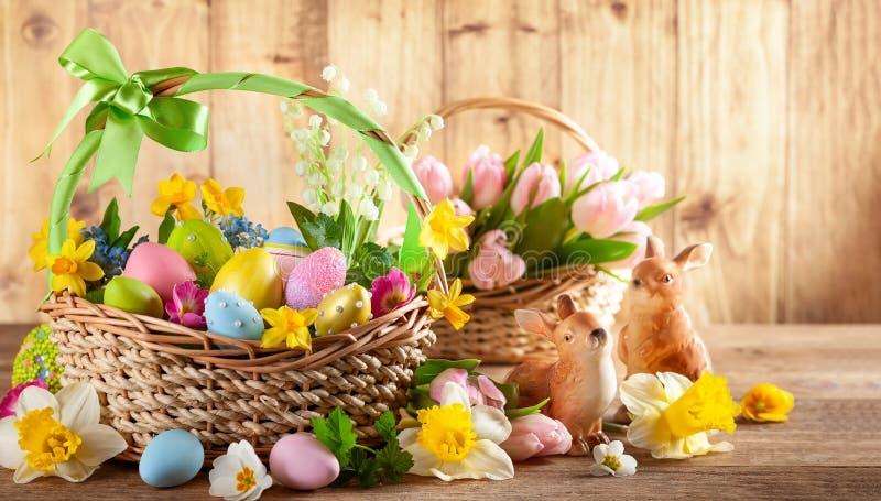 Fleurs de ressort de composition en Pâques et oeufs de pâques colorés dans le panier photographie stock