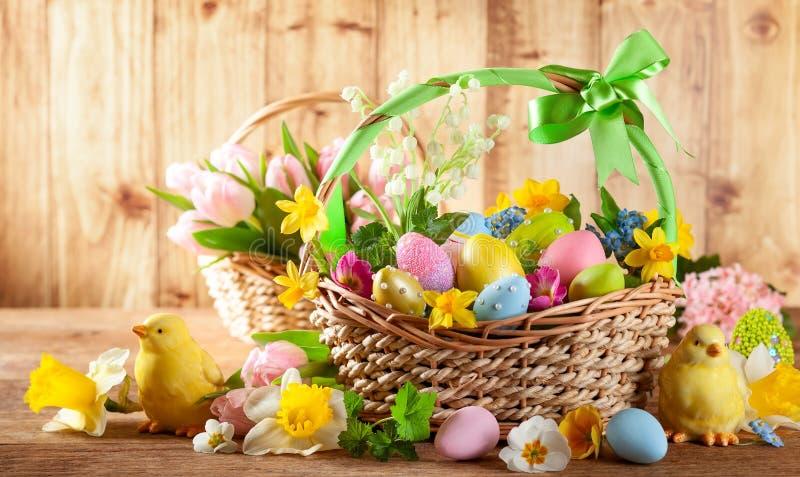 Fleurs de ressort de composition en Pâques et oeufs de pâques colorés dans le panier photo libre de droits