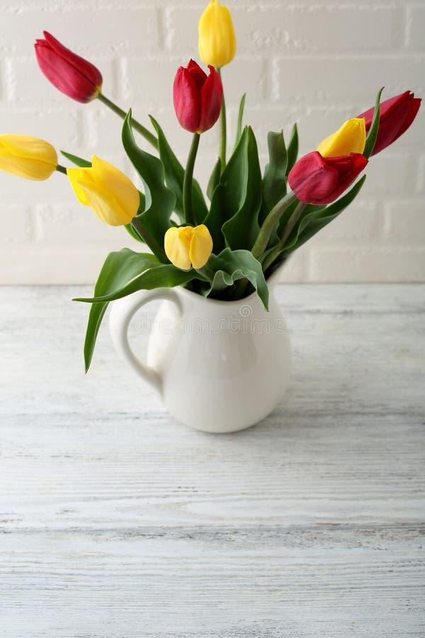Fleurs de ressort dans le broc blanc photographie stock libre de droits