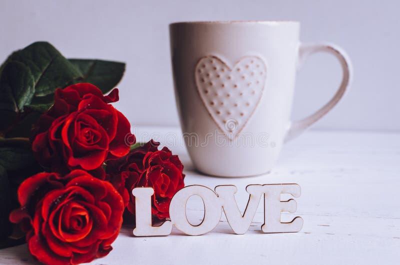 Fleurs de roses rouges avec le mot en bois AMOUR image stock