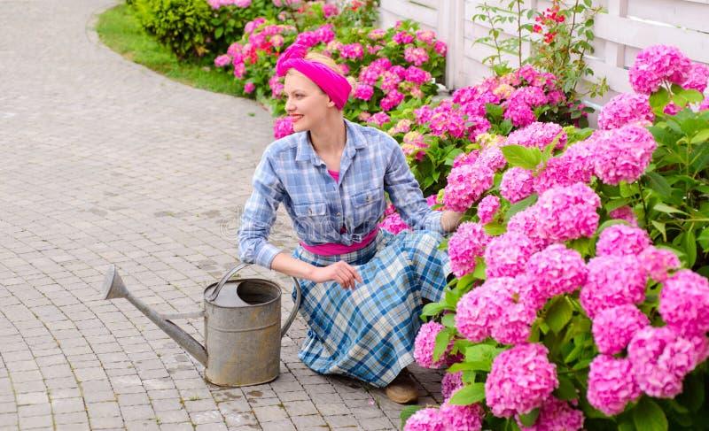 Fleurs de serre chaude Soin et arrosage de fleur sols et engrais soin de femme des fleurs dans le jardin Femme heureux photographie stock libre de droits