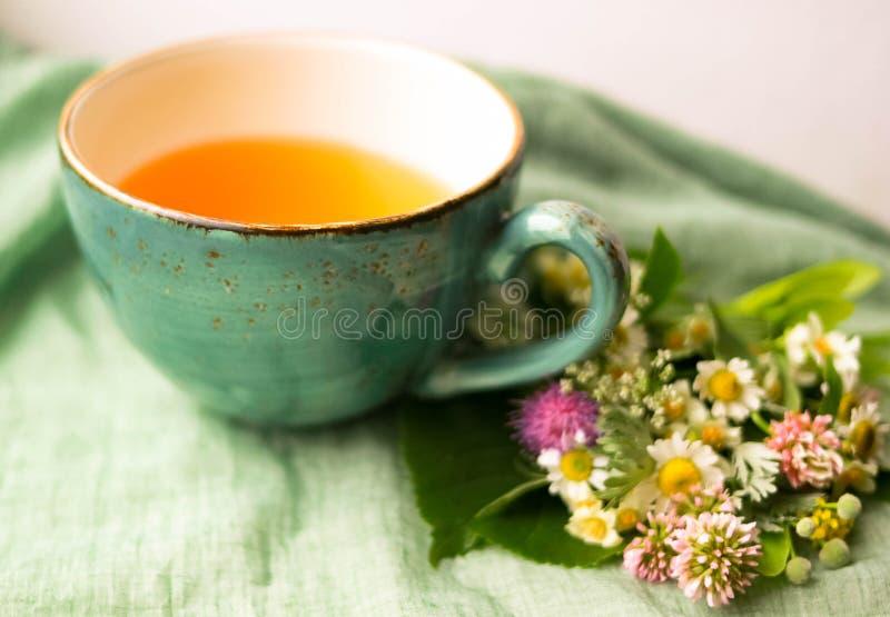 Fleurs de tasse et d'été de tisane de matin près de vue de fenêtre sur le fond vert bleu de serviette de coton image stock
