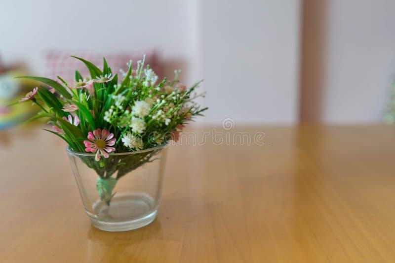 Fleurs en plastique dans le vase sur le backg rose en bois de table et de mur de tache floue photographie stock