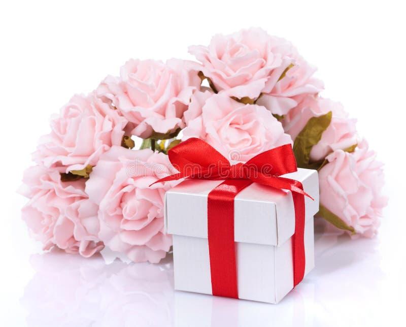 Fleurs et boîte-cadeau avec le ruban rouge et arc roses sur un Ba blanc images libres de droits