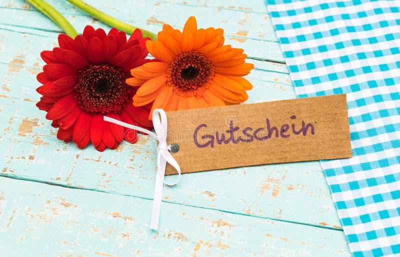 Fleurs et carte avec le mot allemand, le Gutschein, le bon de moyens ou le bon le jour pour de mère ` s ou de ` s de père image libre de droits