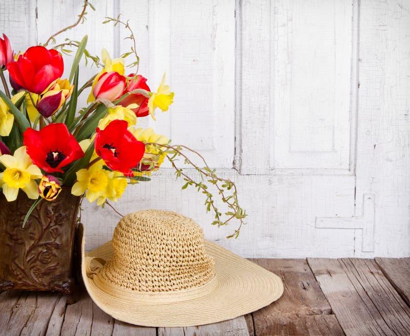 Fleurs et chapeau de paille de ressort photographie stock libre de droits