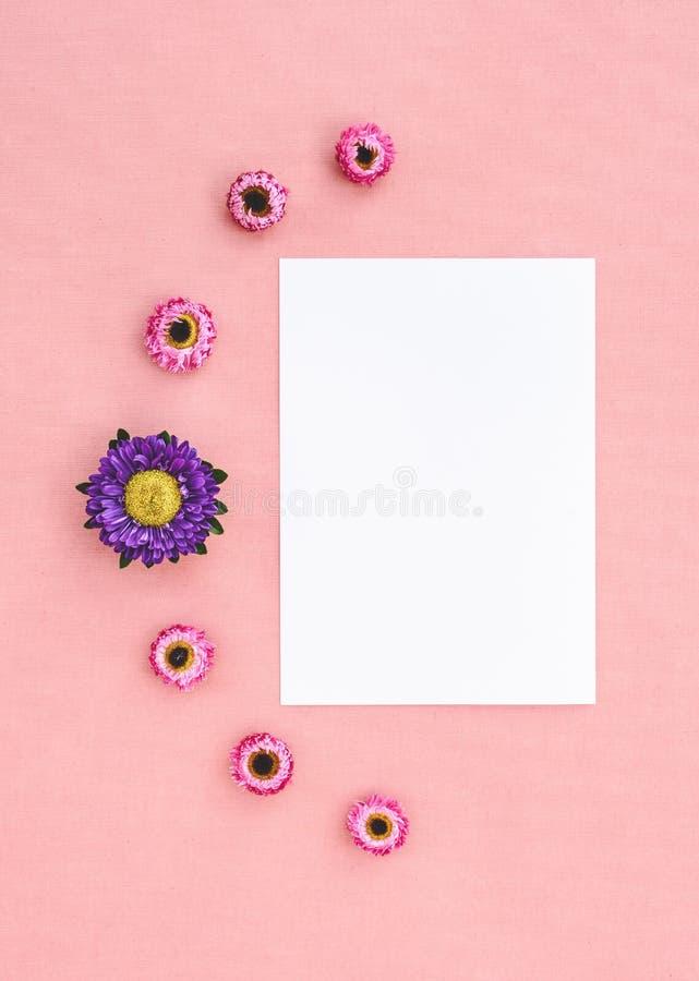 Fleurs et feuille de papier blanche sur la toile rose images stock