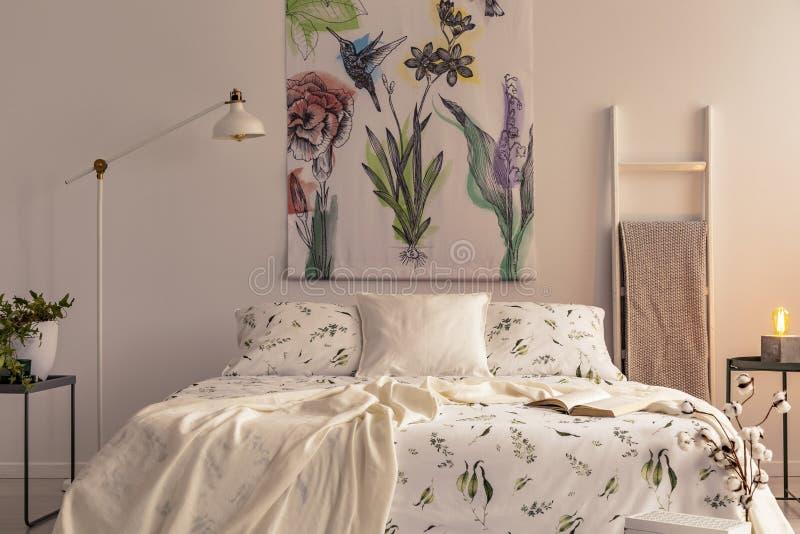Fleurs et un colibri peint sur le tissu au-dessus d'un lit qui est habillé dans la literie de couleur claire de modèle de plantes photographie stock libre de droits