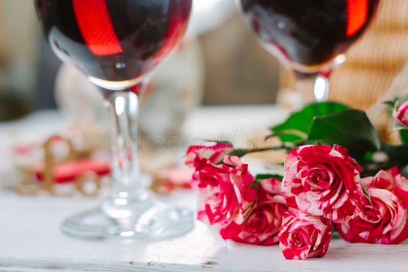 Fleurs et verres de vin sur la célébration de la Saint-Valentin photographie stock