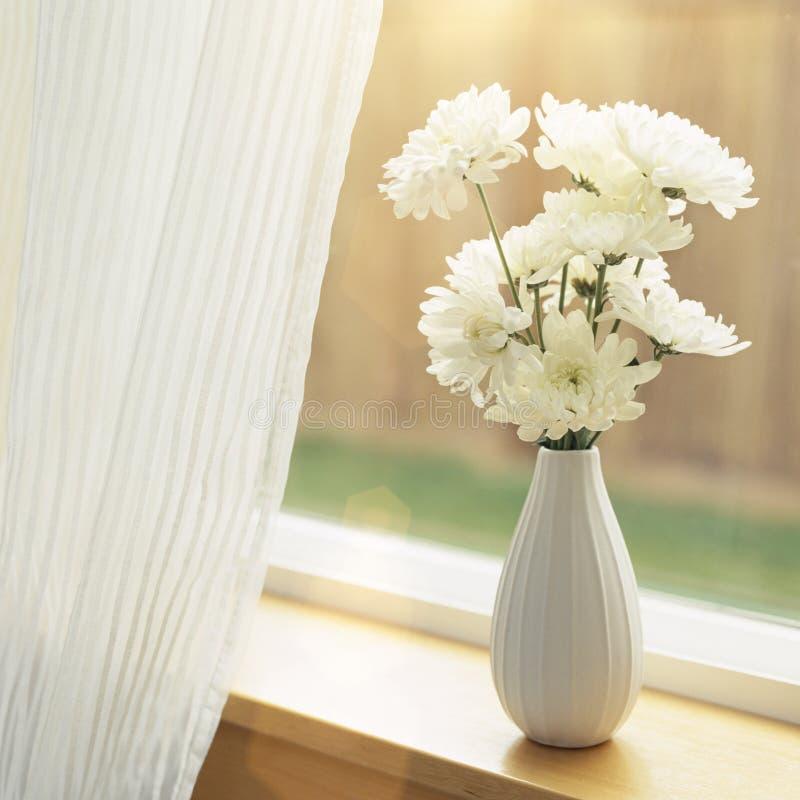 Fleurs fraîches dans le vase sur le rebord de fenêtre avec les bâches de fenêtre pures de rideaux en tissu Décor intérieur simple images libres de droits
