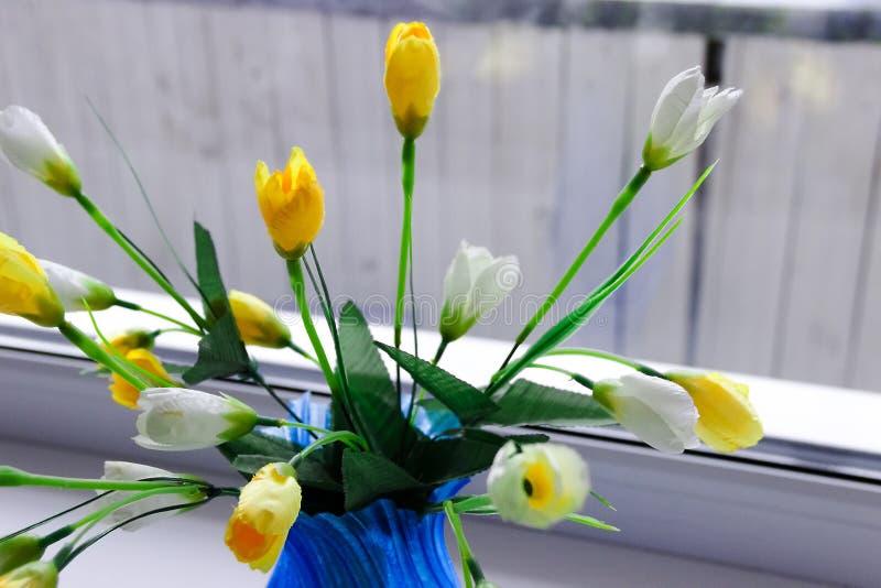 Fleurs jaunes artificielles de tulipe au vase bleu image stock