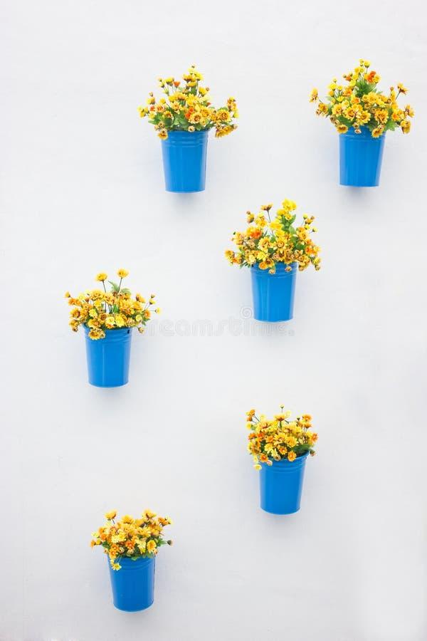 Fleurs jaunes en plastique avec le coup bleu de vase en métal. images stock