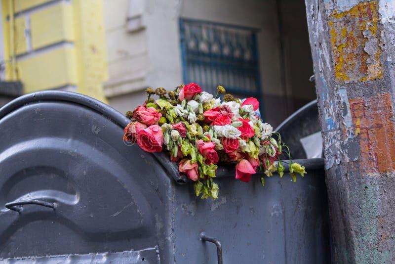 Fleurs jetées se situant dans la poubelle photo libre de droits