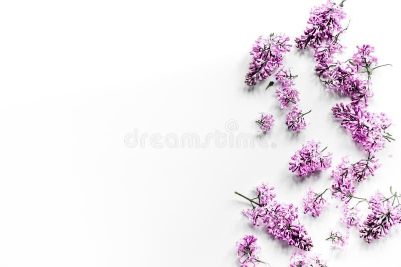 Fleurs lilas de ressort sur la maquette blanche femelle de vue supérieure de fond de siège social de workdesk image libre de droits