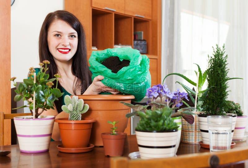 Fleurs mises en pot de transplantation de femme heureuse image stock