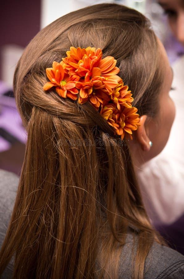 Fleurs oranges dans le cheveu images stock