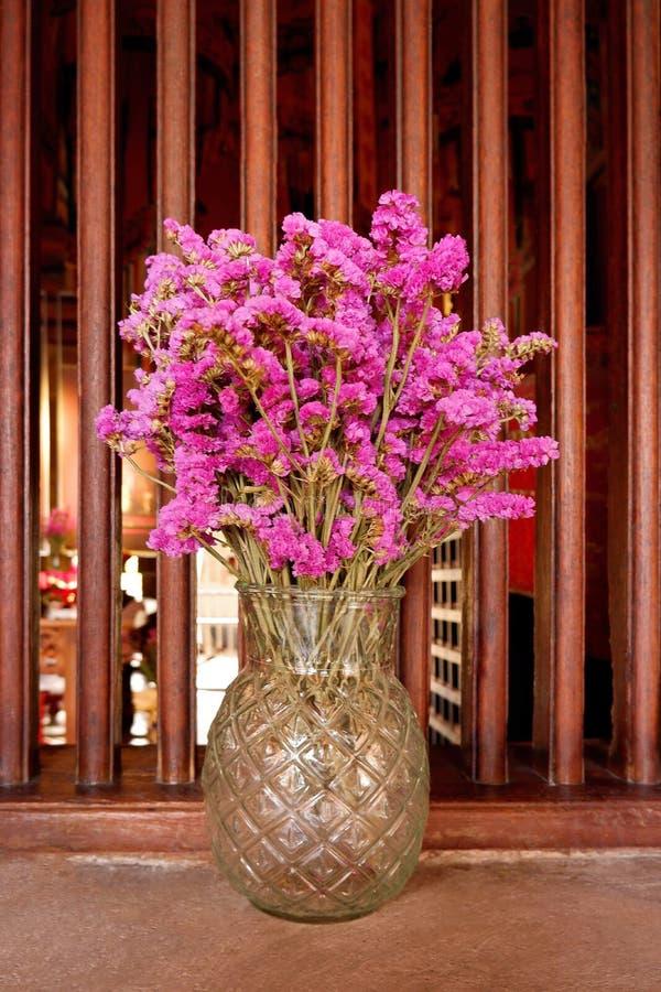Fleurs pourpres sèches montrées dans un vase en verre images libres de droits