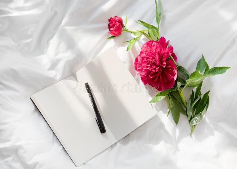 Fleurs restant sur le livre ouvert dans le lit Bonjour romantique Vue sup?rieure photo libre de droits