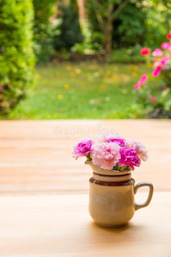 Fleurs roses d'oeillet dans le petit vase en céramique photographie stock