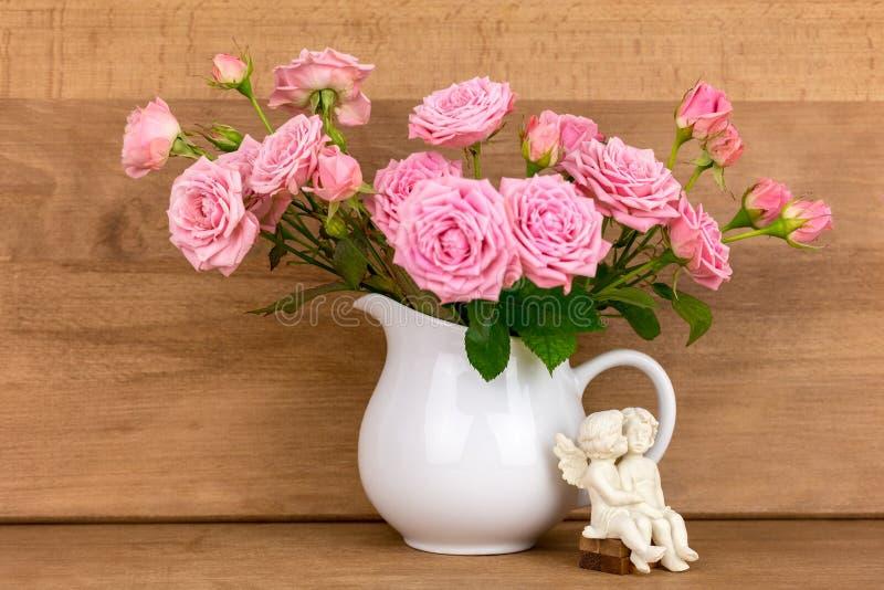 Fleurs roses dans la cruche blanche photo libre de droits