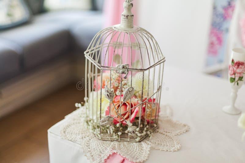 Fleurs roses dans une cage blanche décorative images stock