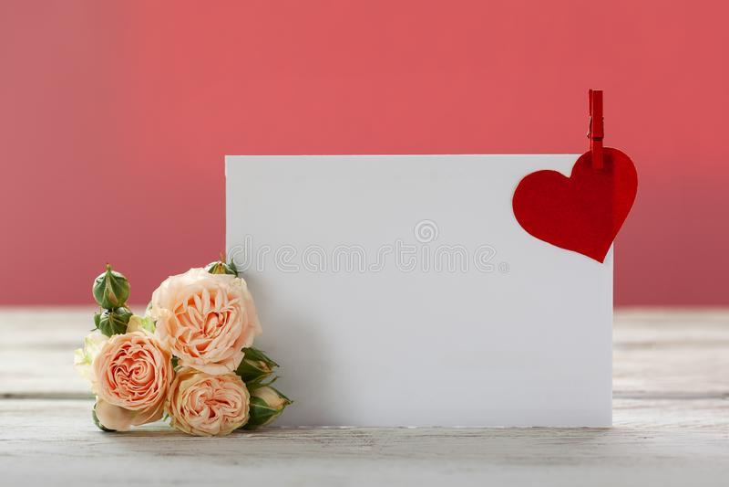 Fleurs roses de roses avec le chèque-cadeau et le coeur de papier rouge sur le fond rose L'espace pour le texte Oncept de Valenti photo libre de droits