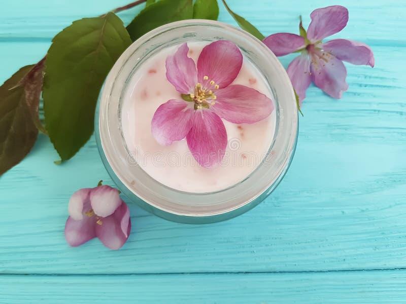 Fleurs roses faites main de lotion de fraîcheur de magnolia cosmétique crème d'essence sur en bois bleu images libres de droits
