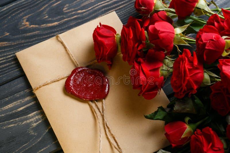 Fleurs roses rouges autour d'enveloppe avec le joint de cire sur la table en bois photographie stock libre de droits