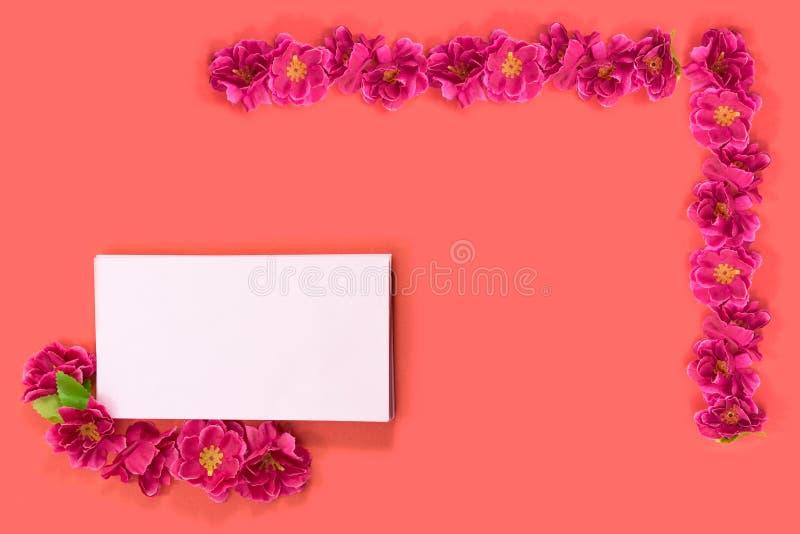 Fleurs rouges avec l'enveloppe rose sur le fond rouge images libres de droits