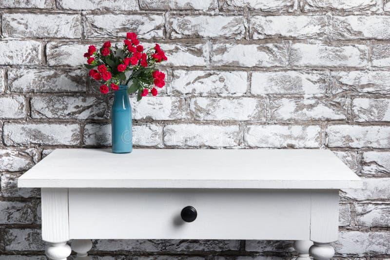 Fleurs rouges dans le vase sur la table sur le fond noir et blanc de mur de briques photo stock