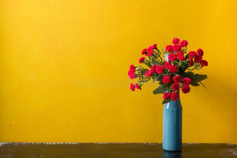 Fleurs rouges dans le vase sur le fond jaune images stock