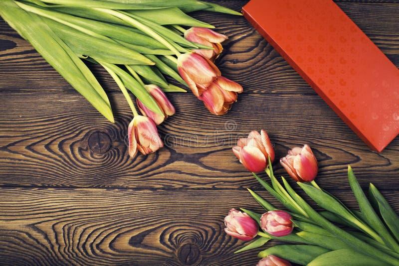 Fleurs rouges de boîte et de tulipe de cadeau sur une table en bois Configuration plate photos libres de droits