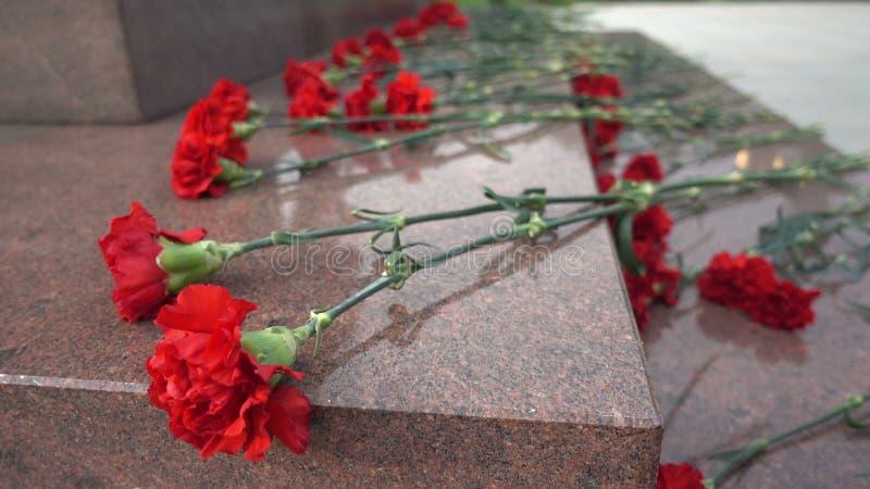 Fleurs rouges sur une pierre tombale photo libre de droits