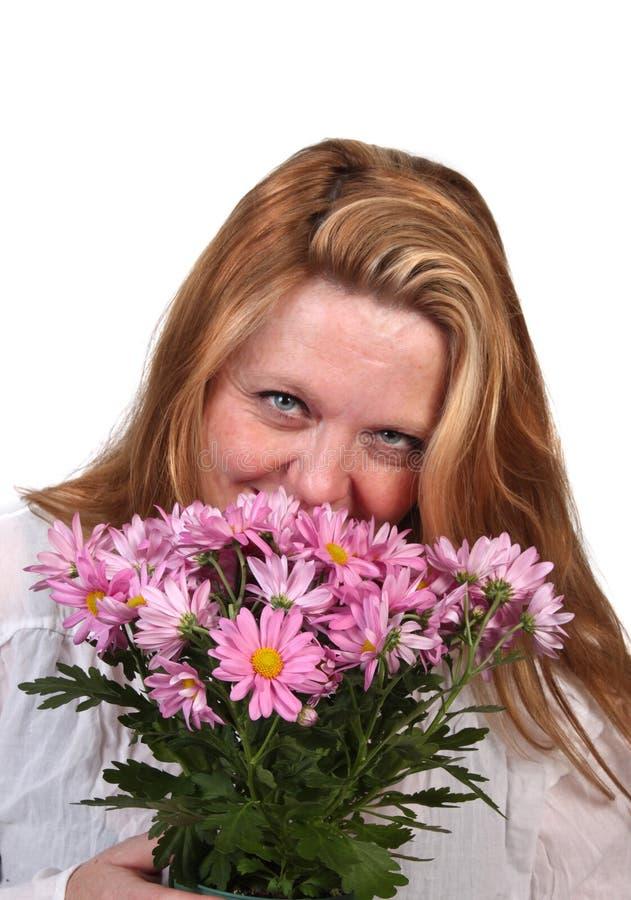 Fleurs sentantes de femme photographie stock libre de droits