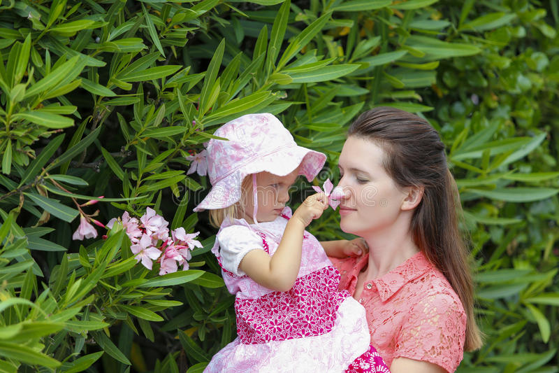 Fleurs sentantes de fille mignonne et de mère heureuse dehors photographie stock