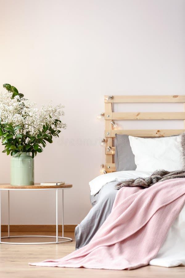 Fleurs sur la table à côté du lit avec la couverture rose et le headbo en bois images stock