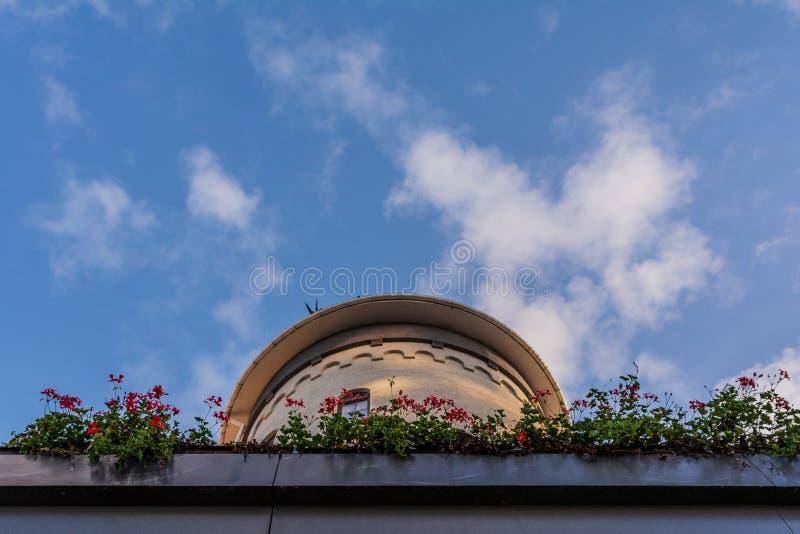 Fleurs sur le balcon et le ciel, tour, nuages, en haut photos stock