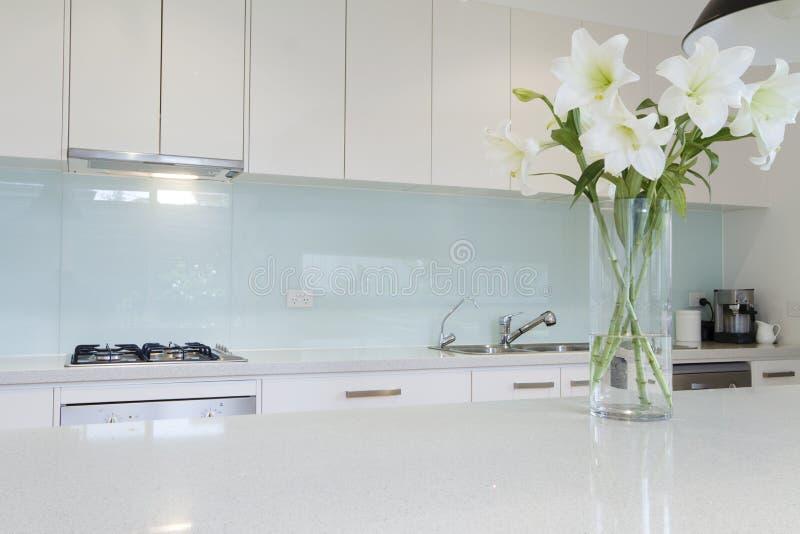 Fleurs sur le banc blanc de cuisine images stock
