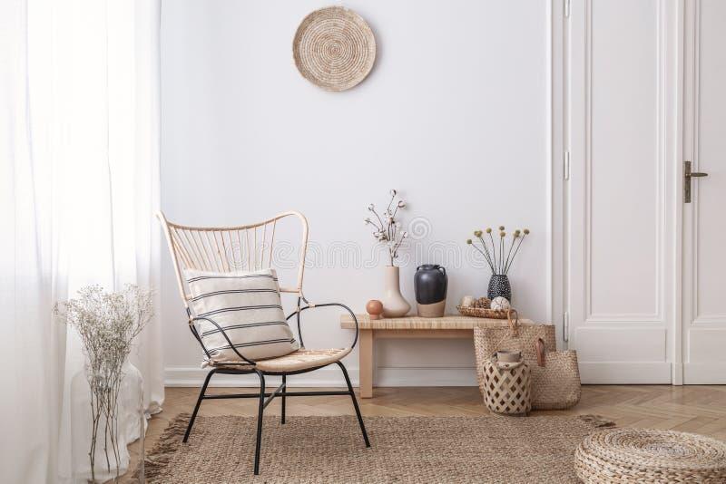 Fleurs sur le tabouret en bois à côté du fauteuil dans l'intérieur blanc de grenier avec le pouf et le plat Photo réelle photographie stock