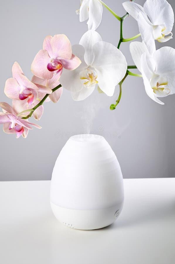 Fleurs ultrasoniques de diffuseur et d'orchidée d'huile sur la table blanche du fond gris image libre de droits
