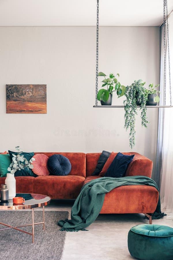 Fleurs vertes sur l'oscillation élégante dans l'intérieur chic de salon avec le sofa faisant le coin avec des oreillers photos stock